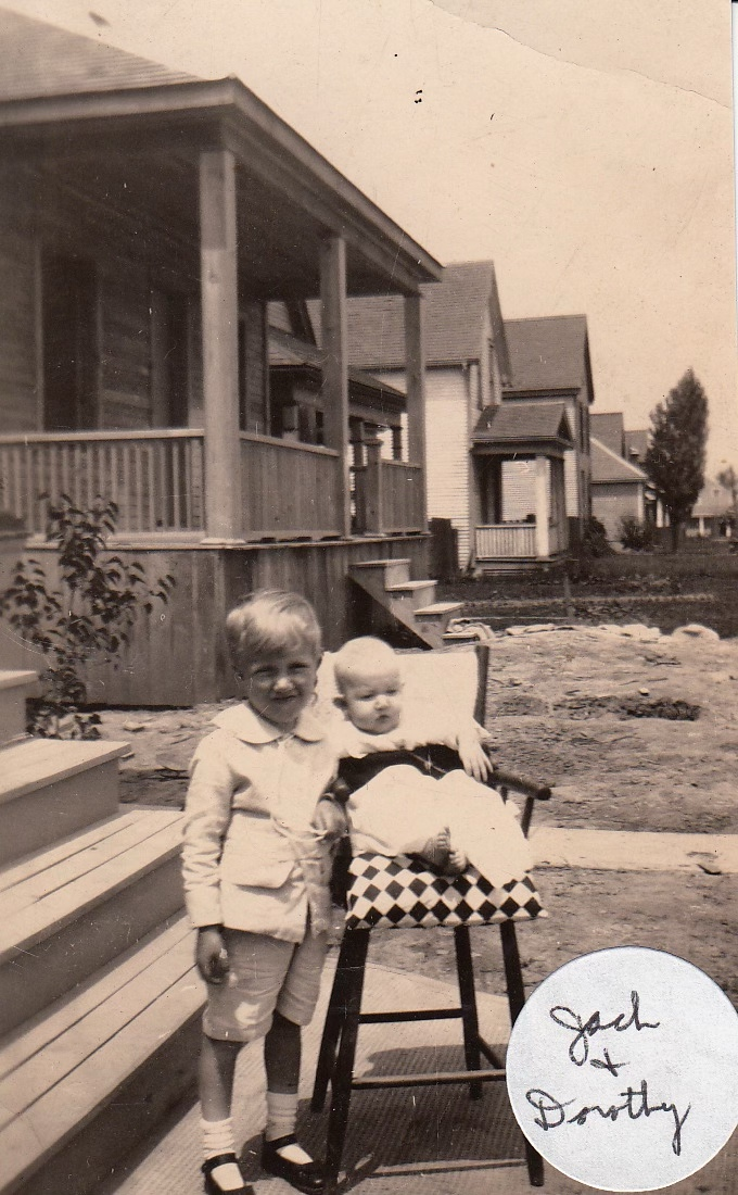 Baby in a wooden highchair, her older brother standing beside her