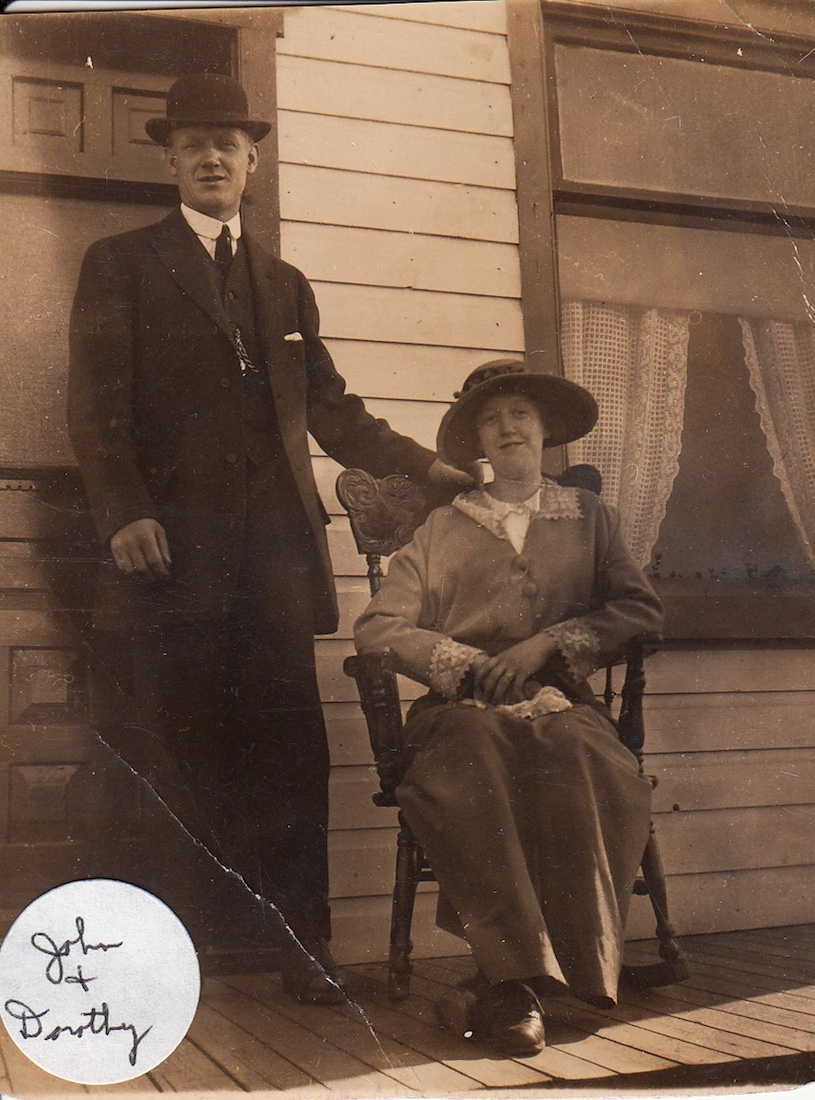 Man and woman in sunday best, woman sitting, man standing