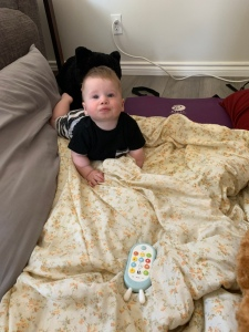 7 month old grandson playing on the floor looking at me